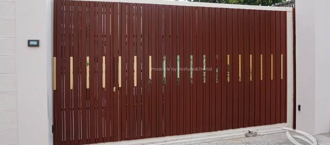 ประตูรั้วสีธรรมชาติตัดกับกรอบเหล็กสีขาว